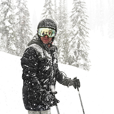 Skier standing in a heavy snowfall at Sun Peaks Resort, Kamloops, British Columbia, Canada