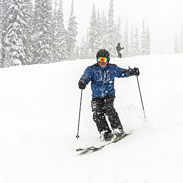 Skier going downhill in a heavy snowfall at Sun Peaks Resort, Kamloops, British Columbia, Canada