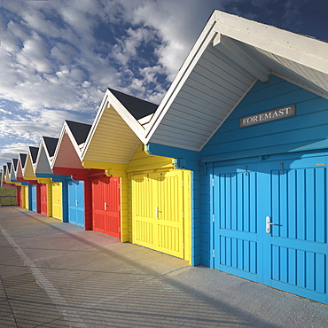Row of colourful beach huts lit by early morning summer sunlight on the seafront at Whitby, North Yorkshire, England, United Kingdom, Europe