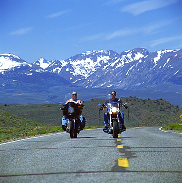 Harley Davidson bikers with snow-capped mountains in background, United States of America, North America