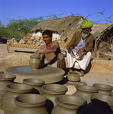 Potter with his father at potter's wheel, Rajasthan, India, Asia