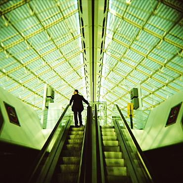 Man on escalator, Charles de Gaulle Airport, Paris, France, Europe