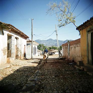 Street scene with man on horseback, Trinidad, Cuba, West Indies, Central America