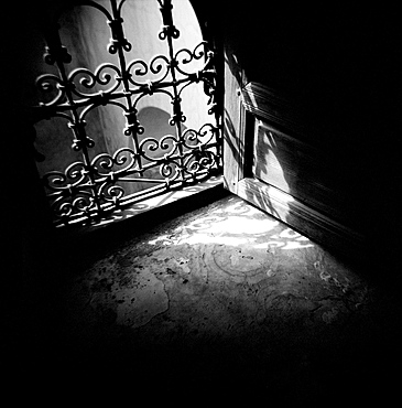 Image taken with a Holga medium format 120 film toy camera of detail of window with ornate iron grille and sunlight streaming through, Morocco, North Africa, Africa