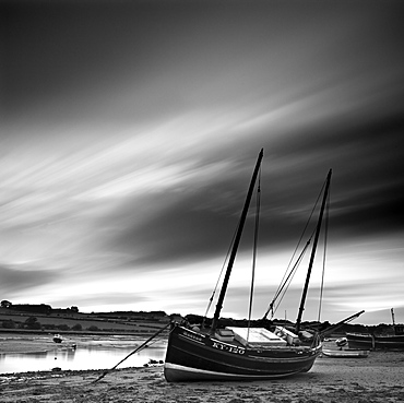 Long exposure used to record moving clouds above old wooden ketch on Aln Estuary at low tide, Alnmouth, Alnwick, Northumberland, England, United Kingdom, Europe