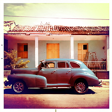 Classic American car parked on a street with traditional house in the background, Trinidad, Cuba, West Indies, Central America