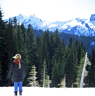 Blonde girl looks at snow covered peaks from the Paradise Lodge, Mount Rainier, Washington State, United States of America (U.S.A.), North America