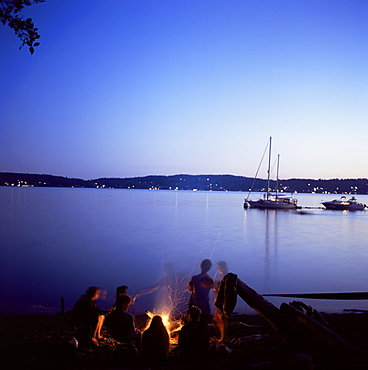 Friends around beach fire, Blake Island, Puget Sound, Washington State, United States of America (U.S.A.), North America