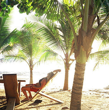 Young woman relaxes on Avellans Beach, Costa Rica, Central America