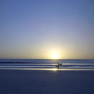 Silhouette of surfer walking on Avellanas Beach, Nicoya Peninsula, Costa Rica, Central America