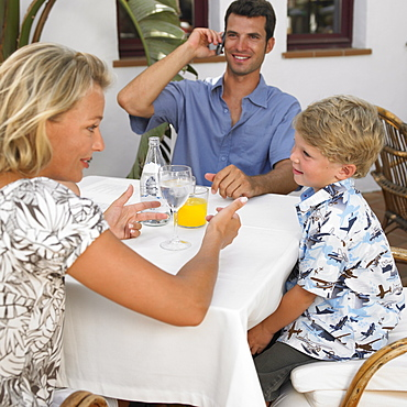 Parents and son (6-8) sitting at an outdoor cafe
