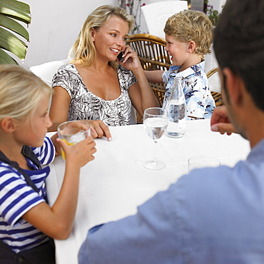 Family sitting at an outdoor cafe, children (6-8)