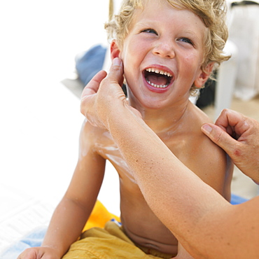 Boy (6-8) on beach having suncream applied