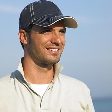 Man on beach wearing baseball cap