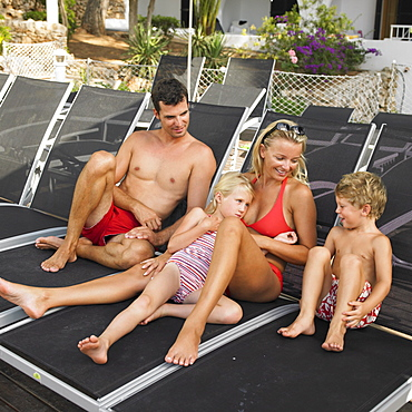 Family relaxing on sunloungers, children (6-8)