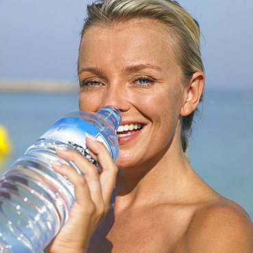 Woman drinking from water bottle on beach, close-up