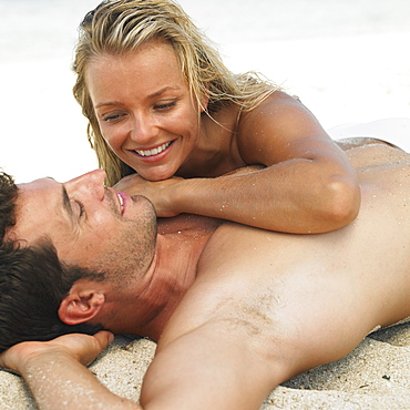 Couple lying together on beach, smiling
