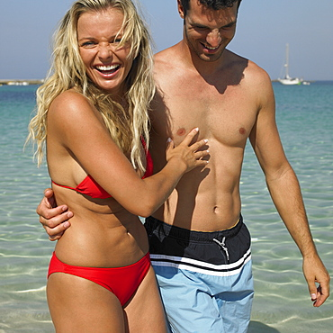 Couple walking on beach, laughing