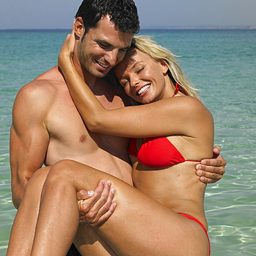 Man carrying woman on beach, smiling