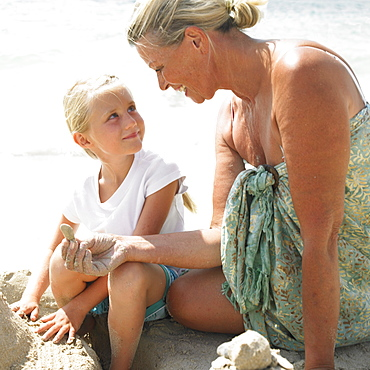 Grandmother and grandaughter (6-8) making a sandcastle on the beach