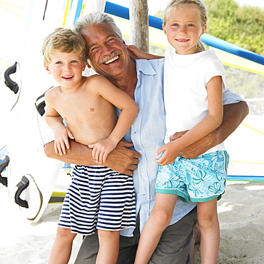 Grandfather and grandchildren (6-8) on beach by windsurfer