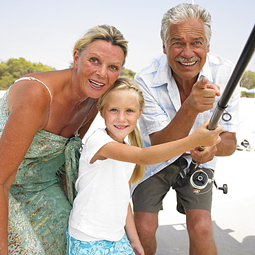 Grandparents and grandaughter (6-8) on beach holding fishing rod