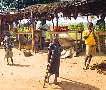 Burundi, Cibitoke Province, Buganda, Market stall selling vegetables beside the road. Francine a 9 year old girl with special needs unable to attend school which is 4 miles a away.