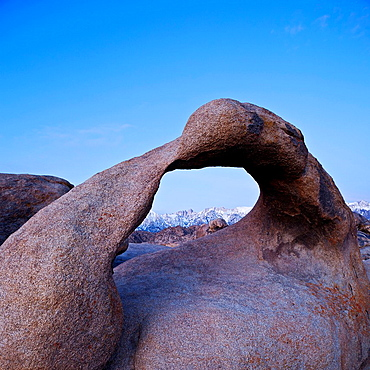 Mobius Arch stone arch in the Alabama Hills with Sierra Nevada mountains in distance, Lone Pine, California