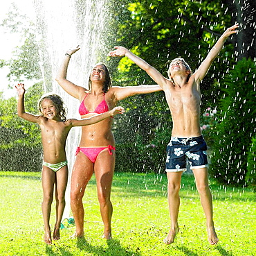 Kids playing under a water jet, Kids playing under a water jet