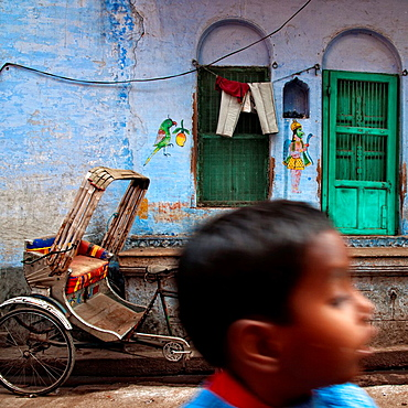 Child running through an alley and rickshaw parked on wall painted wall  Varanassi, India