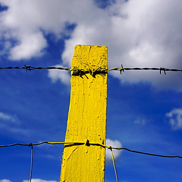 Yellow post, barbed wire, against blue sky with clouds