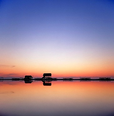 Buildings on stilts at dusk in the North Sea Watt, St Peter Ording, North Frisian, Schleswig-Holstein, Northern Germany, Germany, Europe