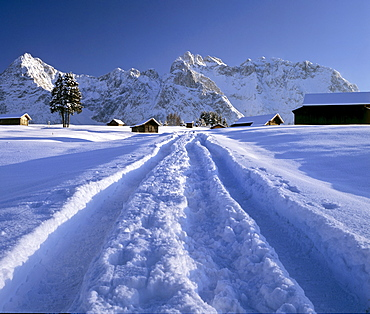 Snowy dirt track in winter, Karwendel mountains, Mittenwald, Upper Bavaria, Germany