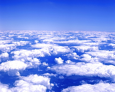 Cumulus clouds in a blue sky viewed from airplane window