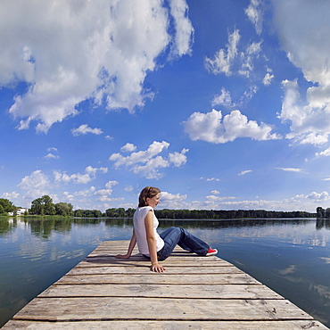 Girl relaxing on a pier of a quarry pond with a reflected cloudy sky, Ingolstadt, Bavaria, Germany, Europe