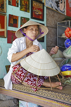 A women weaves a conical hat at a crafts village, Hue, Vietnam, Indochina, Southeast Asia, Asia