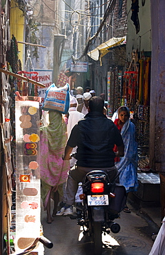 A man attempts to ride his motorbike down a busy street in the oldtown area of Varanasi, India