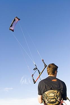 Man holding power kite on Weston-Super-Mare beach, UK