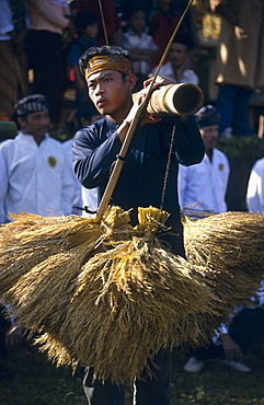 Kasepuhan musician carrying rice bundles at annual rice festival Seren Tahun, West Java, Indonesia