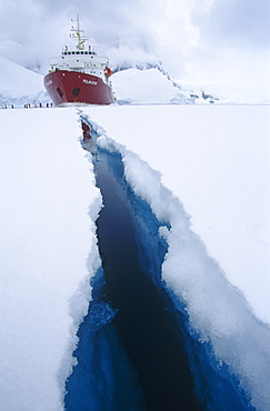 'Polar Star' ecotourism expedition ship with crack in 3m thich ice, created by the ship. Antartic Peninsula, Southern ocean.