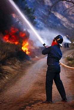 Fireman with hose; Hillside on fire; Coyote Fire; Coyote Fire 1971; Filmore; California