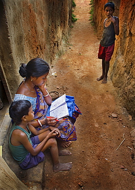 Mother teaching her child in a tribal village in India.