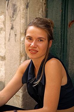 Portrait of a young woman shopkeeper wearing black sleeveless dress, in Dubrovnik, Croatia, Europe