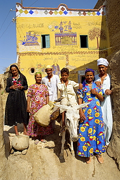 Portrait of a family, three generations, including a boy on a donkey, outside their painted house in the alabaster village of Dra Abul Naga, Egypt, North Africa, Africa
