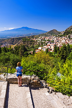 Tourist admiring the view of Mount Etna from Teatro Greco (Greek Theatre), Taormina, Sicily, Italy, Europe
