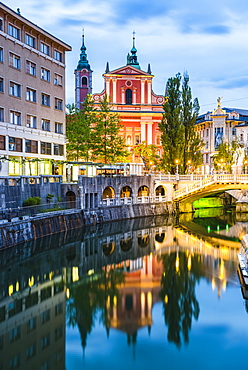 Ljubljana triple bridge (Tromostovje) and Franciscan Church of the Annunciation reflected in Ljubljanica River at night, Ljubljana, Slovenia, Europe