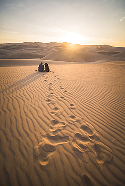 Couple watching the sunset over sand dunes in the desert at Huacachina, Ica Region, Peru, South America - 1109-2530