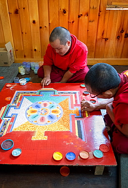 Buddhist monks making a diorama (mandala) with coloured sand, which once made is wiped off to demonstrate transience and impermanence, Bhutan, Asia