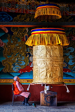 Portrait of elderly Buddhist monk turning prayer wheel, Punakha Dzong, Bhutan, Asia