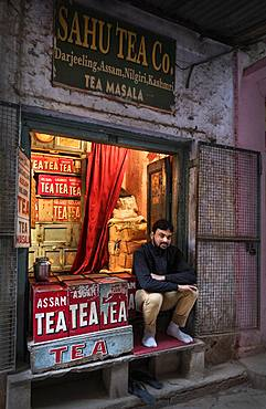 Portrait of an Indian man surrounded by tea tins in his shop, back alleyway near the ghats, Varanasi, Uttar Pradesh, India, Asia